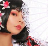 有鞋带爱好者和美丽的花的艺妓在她的黑发,在白色。性感的浅黑肤色的男人 免版税图库摄影