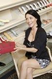 有鞋类箱子的快乐的中间妇女在鞋店 免版税库存照片