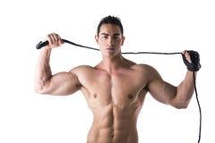 有鞭子和散布的手套的肌肉赤裸上身的年轻人 免版税库存照片