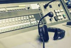 有音乐搅拌器控制台的耳机在演播室葡萄酒过滤器 免版税图库摄影