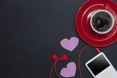 有音乐播放器和红色耳机的红色咖啡杯在黑leath 免版税库存图片