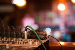 有音量控制器和缆绳的音乐控制台准备好在一个音乐会在客栈,浅dof,低灯照片前 免版税库存图片