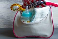 有项目的妇女的提包对孩子的关心:瓶牛奶,一次性尿布,吵闹声,安慰者 库存图片