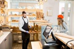 有顾客的卖主在面包店商店 库存照片