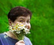 有领域花的微笑的资深妇女 免版税库存图片