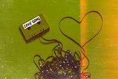 有题字爱情歌曲的卡型盒式录音机在绿色背景的磁带和心脏 减速火箭的与Scratche的技术拉丁文的概念 图库摄影