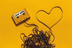 有题字爱情歌曲的卡型盒式录音机在黄色背景的磁带和心脏 减速火箭的技术拉丁文的概念 免版税库存照片