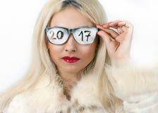 有题字的聪慧的美丽的金发碧眼的女人在玻璃2017年 免版税库存照片