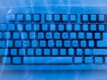 有题字的蓝色光照亮的圣诞快乐键盘 图库摄影
