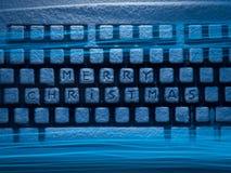 有题字的蓝色光照亮的圣诞快乐键盘 免版税库存图片
