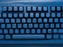 有题字的蓝色光照亮的圣诞快乐键盘 免版税库存照片