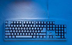 有题字的蓝色光照亮的圣诞快乐键盘 库存照片