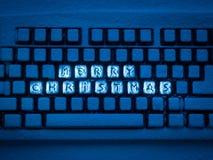 有题字的蓝色光照亮的圣诞快乐键盘 库存图片