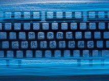 有题字的蓝色光照亮的圣诞快乐键盘 免版税图库摄影