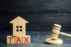 有题字`税`的木房子和法官` s锤击 在房地产,付款的税 惩罚,欠款 taxp记数器  免版税库存图片