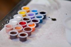 有颜色墨水调色板的塑料杯子 免版税库存图片