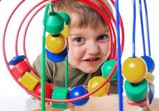有颜色教育玩具的俏丽的婴孩 免版税库存图片