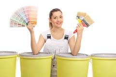 有颜色样片和油漆刷的快乐的女性画家 免版税库存图片