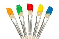 有颜色油漆的五把油漆刷 免版税库存照片