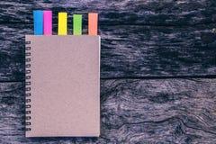 有颜色的笔记本注意在老木桌上的选项 日志为增加 库存图片