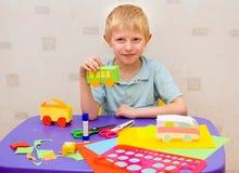 有颜色纸张的男孩 免版税库存照片