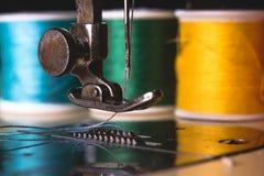 有颜色螺纹和针的老缝纫机,在一个老脏的工作表上 裁缝` s工作表 纺织品或美好布料做 库存图片