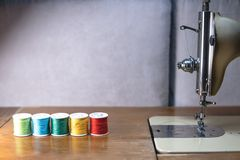 有颜色螺纹的老缝纫机,在一个老脏的工作表上 裁缝` s工作表 纺织品或美好布料做 行业 免版税库存照片