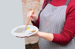 有颜色调色板的女孩在她的手上 在艺术车间 免版税库存照片