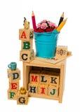 有颜色铅笔的蓝色桶在木字母表块箱子 库存图片