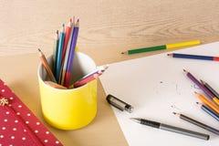 有颜色铅笔的黄色杯子在与玩具的木纹理 免版税库存照片
