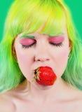 有颜色头发的美丽的女孩拿着与嘴唇的草莓在绿色背景 免版税库存照片