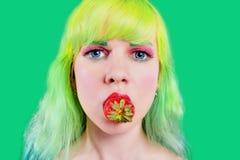 有颜色头发的美丽的女孩拿着与嘴唇的草莓在绿色背景 库存照片