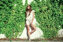 有风吹的长的栗子头发的美丽的轻松的妇女站立在墙壁缠绕了与看的常春藤在旁边 免版税库存图片