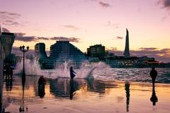 有风多暴风雨的天气的都市沿海岸区在日落 免版税库存照片