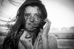 有风海滨的年轻美丽的长的头发妇女 免版税图库摄影
