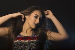 有风的可爱的年轻深色的妇女在头发和黑暗的构成 库存照片
