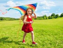 有风筝的愉快的女孩 免版税库存照片