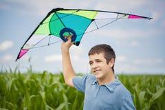 有风筝的男孩在麦地 免版税库存照片