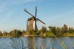 有风车的小孩堤防运河 日落在更加亲切荷兰的村庄 免版税库存照片