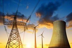 有风轮机和电定向塔的核电站在日落 免版税库存照片