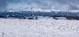 有风轮机和积雪的峰顶的冬天奥地利阿尔卑斯全景 库存照片