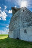 有风轮机的老被风化的谷仓在背景中 免版税库存照片