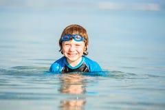 有风镜的愉快的微笑的男孩在浅的游泳 库存图片