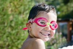 有风镜的逗人喜爱的小孩笑在水池的 免版税库存图片