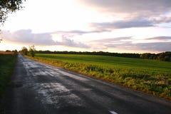 有风雨如磐的云彩的乡下公路在日落农村场面 免版税库存照片