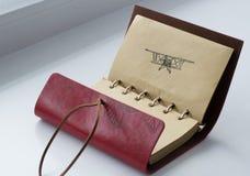 有飞机的笔图片的皮革笔记本 免版税库存图片