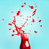 有飞溅的红色汁液或圆滑的人玻璃瓶在绿松石背景,正面图 库存照片