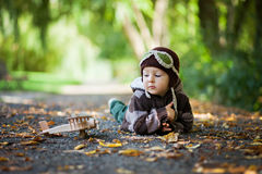 有飞行员帽子的小男孩,说谎在地面上在公园 库存照片