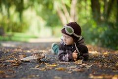 有飞行员帽子的小男孩,说谎在地面上在公园 免版税库存照片