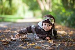 有飞行员帽子的小男孩,说谎在地面上在公园 图库摄影